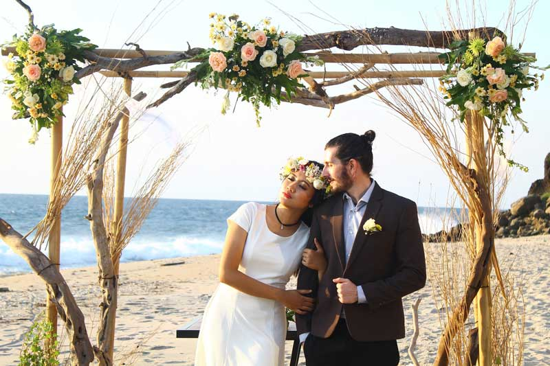 bride wears flower crown at bohemian beach wedding